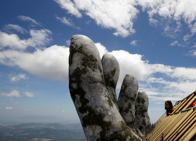 A tourist looks out near a giant hand structure at the Gold Bridge on Ba Na hill near Danang city, Vietnam on August 1, 2018. (Photo by Reuters/Kham)