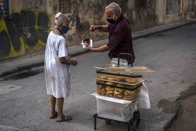 Wearing masks as a precaution against the spread of the new coronavirus, a vendor gives a complimentary, homemade guava pastry to an elderly woman in Havana, Cuba, Friday, March 19, 2021. (Photo by Ramon Espinosa/AP Photo)