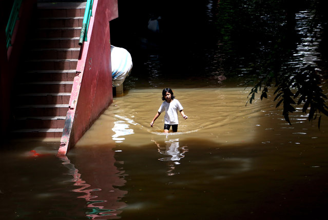 A young girl makes her way through a flooded neighborhood in Jakarta, Indonesia, Tuesday, February 10, 2015. (Photo by Tatan Syuflana/AP Photo)