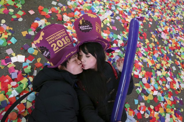Revelers kiss as they pose for a picture while laying on the confetti covered ground during New Year's celebrations in Times Square in the Manhattan borough of New York January 1, 2016. (Photo by Andrew Kelly/Reuters)