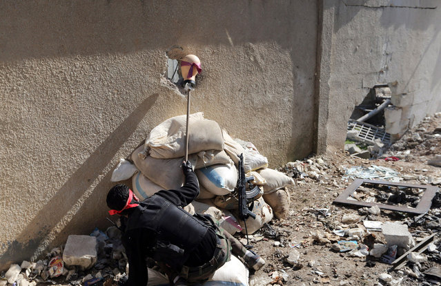 """A """"Free Syrian Army"""" fighter holds the head of a mannequin up to a hole in a wall of a Syrian Army base to attract and locate a sniper during heavy fighting in the Arabeen neighborhood of Damascus, on February 3, 2013. (Photo by Goran Tomasevic/Reuters)"""