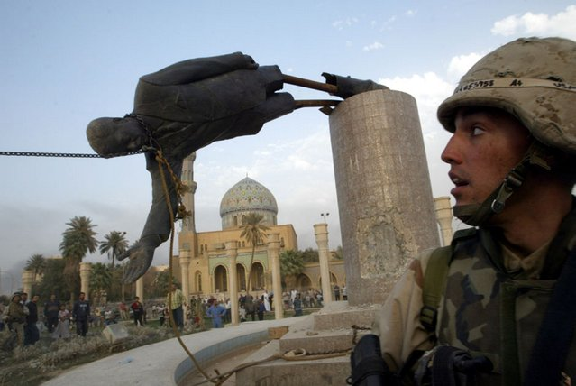 U.S. Marine Corp Assaultman Kirk Dalrymple watches as a statue of Iraq's President Saddam Hussein falls in central Baghdad in this April 9, 2003 file photo. U.S. troops pulled down a 20-foot (six-metre) high statue of President Saddam Hussein in central Baghdad and Iraqis danced on it in contempt for the man who ruled them with an iron grip for 24 years. (Photo by Goran Tomasevic/Reuters)