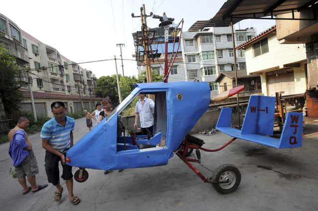 Wen Jiaquan (2nd L), 54-year-old motorcycle mechanic, moves his self-made helicopter in Qingping township of Chongqing municipality, July 28, 2013. Wen and his family spent over 10,000 yuan (1,630 USD) and more than three months to build this 4.2-metre-long, 2.8-metre-high helicopter using mostly motorcycle components and a used car engine, local media reported. (Photo by Reuters/Stringer)