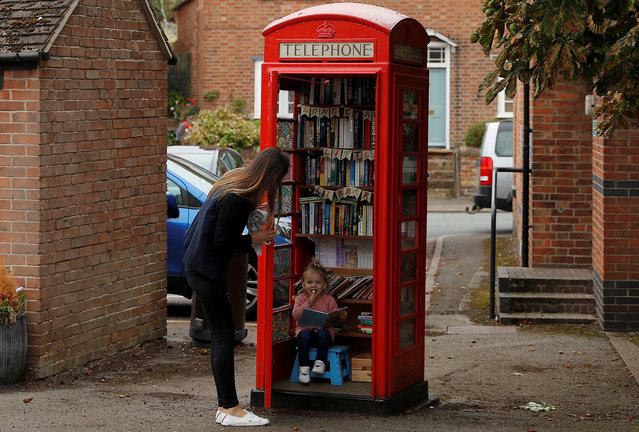 Aria Casey aged 2 looks at books in a library inside a former British Telecom phone box in Long Clawson, Britain September 10, 2018. (Photo by Darren Staples/Reuters)
