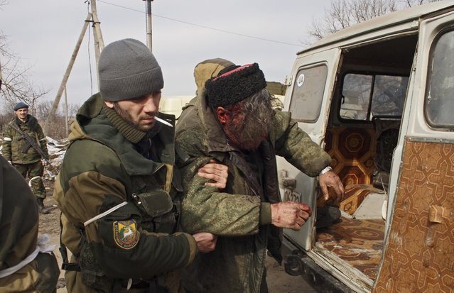 A wounded Cossack is carried away by fellow fighters after his car hit a land mine in the east Ukraine town of Debaltseve on Thursday, February 19, 2015. After weeks of relentless fighting, the embattled Ukrainian rail hub of Debaltseve fell Wednesday to Russia-backed separatists, who hoisted a flag in triumph over the town. (Photo by Peter Leonard/AP Photo)