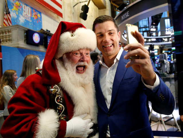 Tom Farley, president of the NYSE Group, poses for a selfie with Santa Claus who rang the opening bell to celebrate the Macy's 90th Annual Thanksgiving Day Parade at the New York Stock Exchange (NYSE) in New York City, U.S., November 23, 2016. (Photo by Brendan McDermid/Reuters)
