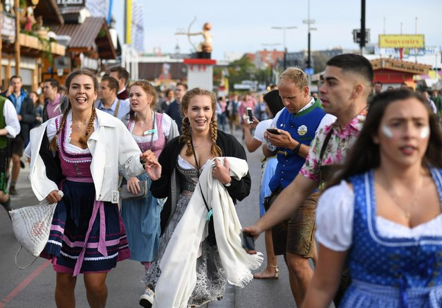 Visitors run to get a spot at the Oktoberfest area at the opening day of the 185th Oktoberfest in Munich, Germany September 22, 2018. (Photo by Andreas Gebert/Reuters)