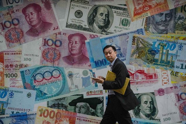 A man walks past a display showing bank notes of different currencies in Hong Kong on November 9, 2016. Share markets plunged on November 9 and the dollar tumbled against the yen and the euro as Donald Trump was elected US president, in a stunning upset with major implications for the world economy. (Photo by Anthony Wallace/AFP Photo)