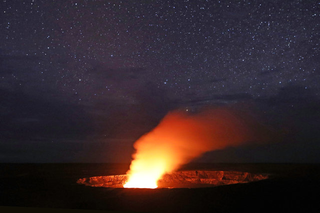 Stars shine above as a plume rises from the Halemaumau crater, illuminated by glow from the crater's lava lake, within the Kilauea volcano summit at the Hawaii Volcanoes National Park on May 9, 2018 in Hawaii Volcanoes National Park, Hawaii. (Photo by Mario Tama/Getty Images)
