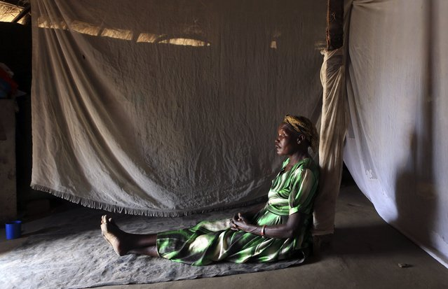 A woman, who did not want to be identified, sits on a floor inside her house in Odek village, north of Uganda capital Kampala February 14, 2015. (Photo by James Akena/Reuters)