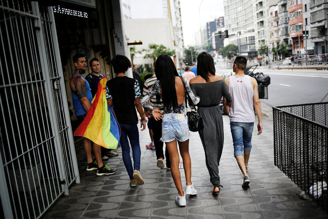 Men look at Gaby, 18, Natalia, 20, Fernanda, 20, and Aleksander, 23, who are among members of lesbian, gay, bisexual and transgender (LGBT) community, that have been invited to live in a building that the roofless movement has occupied, walk on a street in Sao Paulo, Brazil, November 16, 2016. (Photo by Nacho Doce/Reuters)