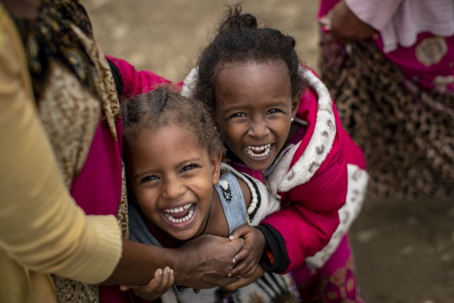 Two displaced Tigrayan girls giggle next to their mother, left, as their photograph is taken outside the Hadnet General Secondary School which has become a makeshift home to thousands displaced by the conflict, in Mekele, in the Tigray region of northern Ethiopia Wednesday, May 5, 2021. The Tigray conflict has displaced more than 1 million people, the International Organization for Migration reported in April, and the numbers continue to rise. (Photo by Ben Curtis/AP Photo)