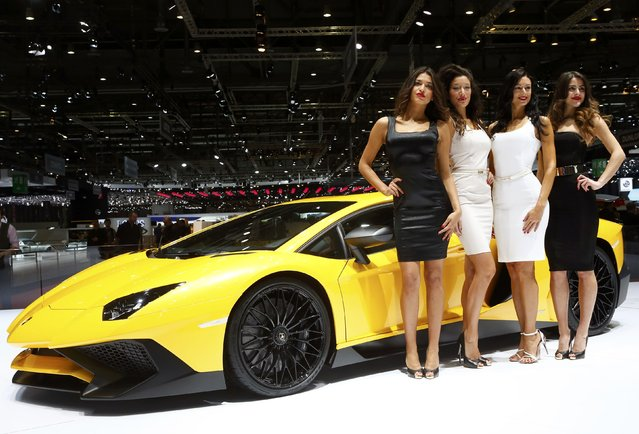 Models pose next to a Lamborghini Aventador SV sports car during the second press day ahead of the 85th International Motor Show in Geneva March 4, 2015.  REUTERS/Arnd Wiegmann