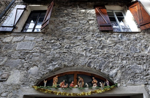 A Nativity scene is seen at the window of a house in the medieval mountain village of Luceram as part of Christmas holiday season, France, December 15, 2016. (Photo by Eric Gaillard/Reuters)