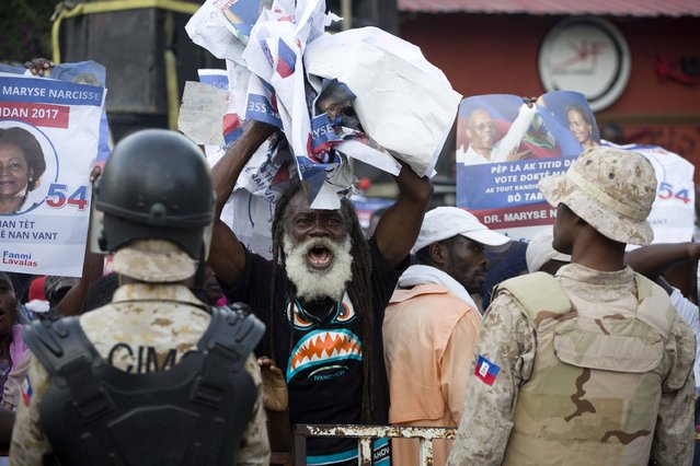 A supporter of presidential candidate Maryse Narcisse of Fanmi Lavalas political party, holds up campaign posters in front of a police during a protest in Port-au-Prince, Haiti. Friday December 16, 2016. Supporters of losing presidential candidates are protesting the results of the election projecting as the winner Jovenel Moise, the  handpicked candidate of Haiti's previous elected leader. (Photo by Dieu Nalio Chery/AP Photo)