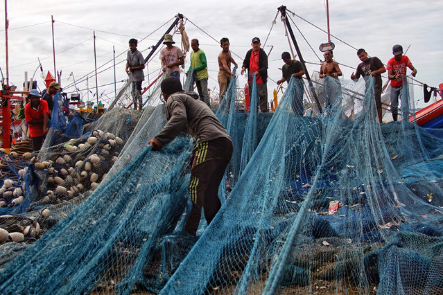 Fishermen gather to repair their nets as high waves prevent them from going out to sea at a fishing village in Lhokseumawe, Aceh on May 28, 2021. (Photo by Azwar Ipank/AFP Photo)