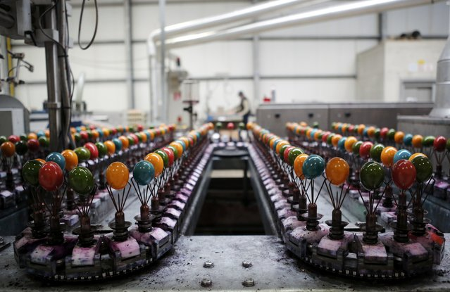 Cooked eggs are coloured on the production line at the Schrall coloured eggs company in the Austrian Village of Diendorf March 16, 2015. Schrall is one of Austria's biggest Easter and coloured eggs producers and makes between eight and 10 million coloured eggs throughout year. (Photo by Leonhard Foeger/Reuters)