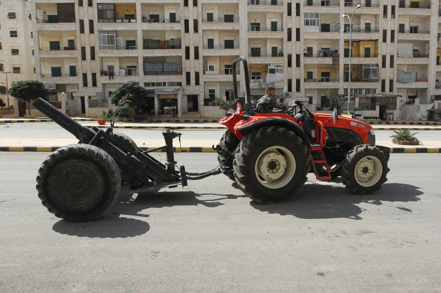 A Free Syrian Army fighter rides a tractor as he moves a homemade cannon in Ashrafieh, Aleppo September 25, 2013. (Photo by Muzaffar Salman/Reuters)