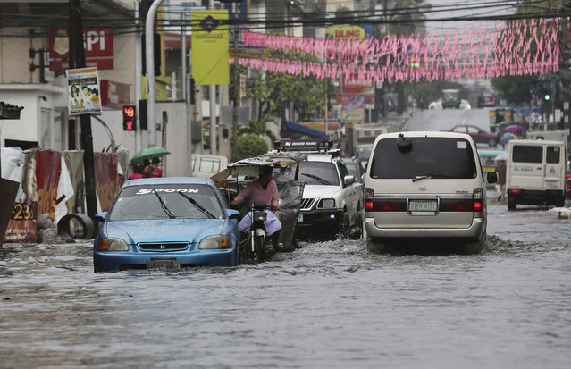 Vehicles navigate a flood-prone area caused by rains from Typhoon Nock-Ten in Quezon city, north of Manila, Philippines on Monday, December 26, 2016. (Photo by Aaron Favila/AP Photo)