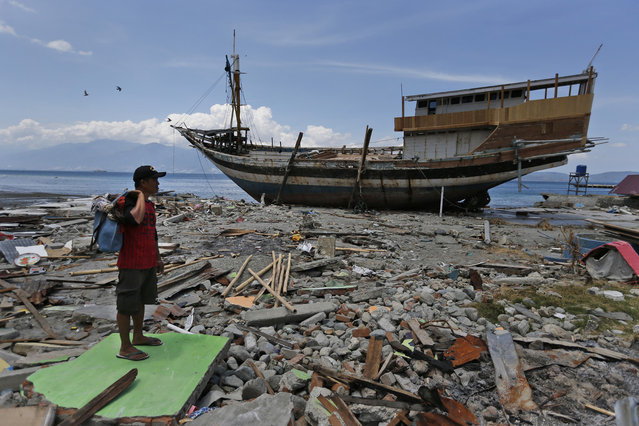 A man carries his belongings he scavenged from the ruins of his house as a boat swept ashore by tsunami rests on the beach in Wani village on the outskirt of Palu, Central Sulawesi, Indonesia, Wednesday, October 10, 2018. A 7.5 magnitude earthquake rocked Central Sulawesi province on Sept. 28, triggering a tsunami and mudslides that killed a large number of people and displaced tens of thousands of others. (Photo by Dita Alangkara/AP Photo)
