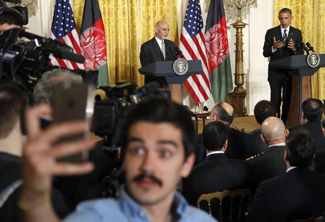"An Afghan journalist takes a ""selfie"" as U.S. President Barack Obama (R) holds a joint news conference with Afghanistan's President Ashraf Ghani (C) at the White House in Washington March 24, 2015. (Photo by Jonathan Ernst/Reuters)"
