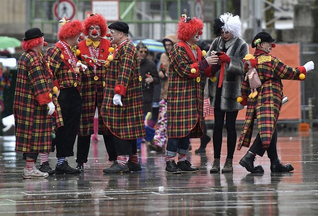 Clowns standing in the rain during the start of the street carnival in Cologne, Germany, on Thursday, February 4, 2016. (Photo by Martin Meissner/AP Photo)