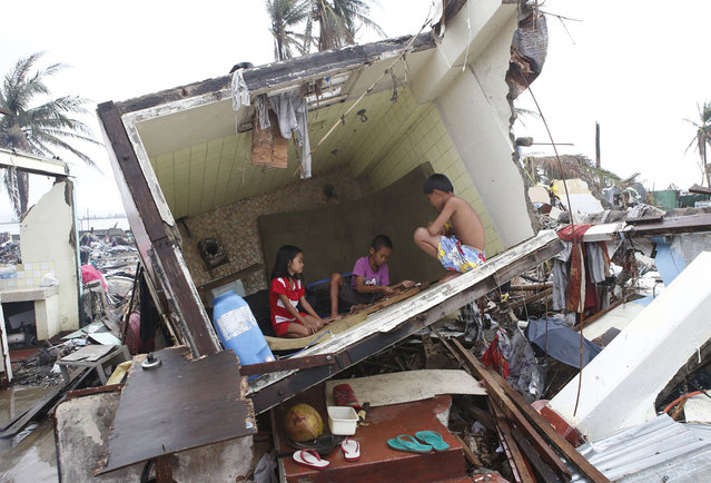 """Typhoon survivors play a game called """"Sungka"""" inside the bathroom of a house, toppled by Super Typhoon Haiyan that battered Tacloban city nearly two weeks ago, in central Philippines November 21, 2013. (Photo by Erik De Castro/Reuters)"""
