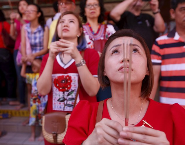 Women pray at a temple during Chinese New Year celebrations in Kuala Lumpur, Malaysia, February 8, 2016. (Photo by Olivia Harris/Reuters)