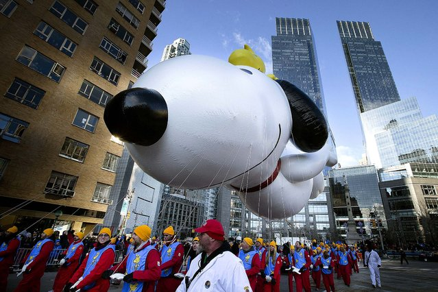 A giant Snoopy balloon is marched through Columbus Circle. After fears the balloons could be grounded if sustained winds exceeded 23 mph, Snoopy, Spider-Man and the rest of the iconic balloons received the all-clear from the New York Police Department to fly between Manhattan skyscrapers. (Photo by John Minchillo/Associated Press)