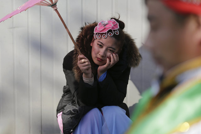 Performers wait for their turn to go onto the stage at the Longtan park as the Chinese Lunar New Year, which welcomes the Year of the Monkey, is celebrated in Beijing, China February 9, 2016. (Photo by Damir Sagolj/Reuters)