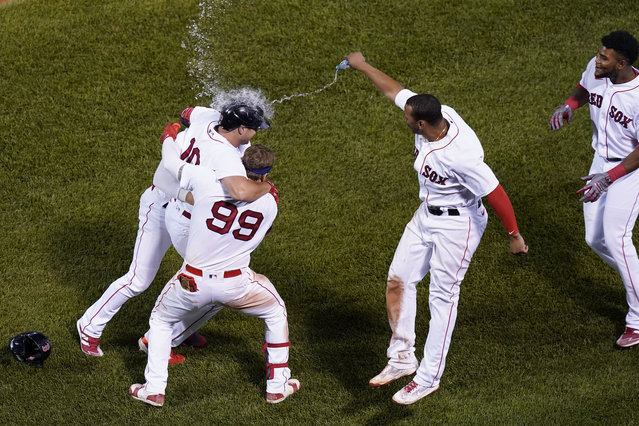 Boston Red Sox's Hunter Renfroe (10) is congratulated after he drove in the winning run with a sacrifice fly in the 10th inning of the team's baseball game against the New York Yankees at Fenway Park, Thursday, July 22, 2021, in Boston. The Red Sox won 5-4. (Photo by Elise Amendola/AP Photo)