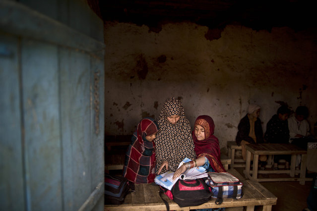 Afghan refugee schoolgirls attend a class at a makeshift school on the outskirts of Islamabad, Pakistan, Friday, February 20, 2015. (Photo by Muhammed Muheisen/AP Photo)