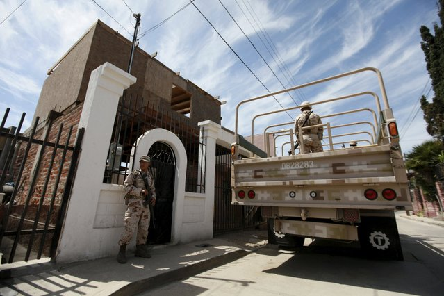 Soldiers stand guard outside a house, where a suspected drug tunnel under construction was located, during a media tour by Mexican Army in Tijuana April 7, 2015. (Photo by Reuters/Stringer)