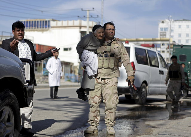 A member of the Afghan security force holds a woman while rescuing her from the site of an attack in Mazar-i-Sharif, April 9, 2015. Militants armed with rocket-propelled grenades and other weapons stormed a court in Afghanistan's northern city of Mazar-i-Sharif on Thursday, killing the district police chief and two other officers, authorities said. (Photo by Anil Usyan/Reuters)