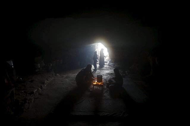 Palestinians warm themselves by a fire inside a cave they live in, during a snow storm in West Bank village of Mufagara, south of Hebron January 27, 2016. (Photo by Mussa Qawasma/Reuters)