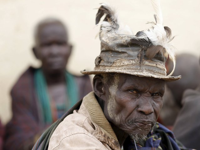A Karamojong tribesman sits as he waits to vote at a polling station during elections in a village near the town of Kaabong in Karamoja region, Uganda February 18, 2016. (Photo by Goran Tomasevic/Reuters)
