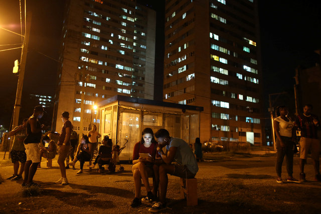 Carolina Gutierrez (center L), 17, and Neuil Valdez, 18, use mobile phones to connect to the internet at a hotspot in downtown Havana, Cuba, December 12, 2016. (Photo by Alexandre Meneghini/Reuters)