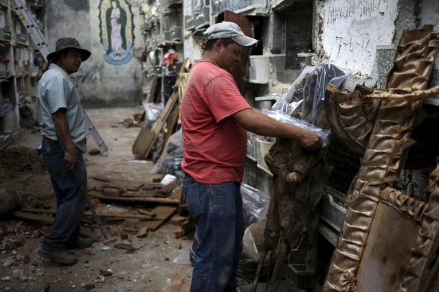 A grave cleaner wraps a mummified body in a plastic bag during exhumation work at the General Cemetery in Guatemala City, April 15, 2015. (Photo by Jorge Dan Lopez/Reuters)