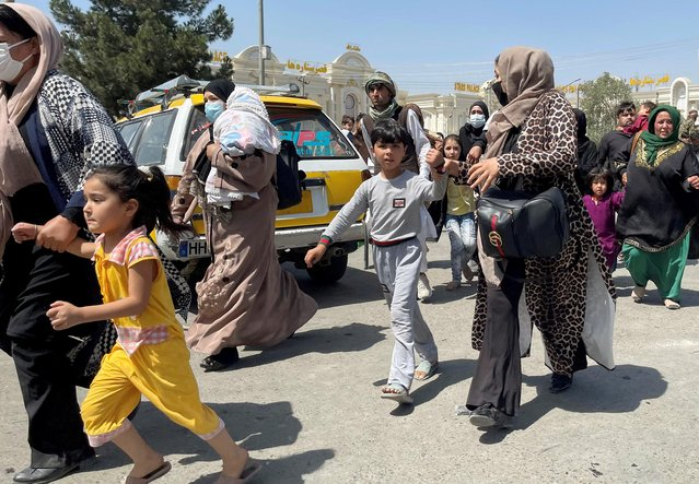 Women with their children try to get inside Hamid Karzai International Airport in Kabul, Afghanistan on August 16, 2021. (Photo by Reuters/Stringer)