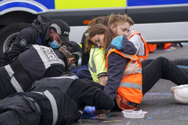 Police officers work to free protesters who had glued themselves to a slip road at Junction 4 of the A1(M), near Hatfield, UK on Monday, September 20, 2021, where climate activists carried out a further action after demonstrations which took place last week across junctions in Kent, Essex, Hertfordshire and Surrey. (Photo by Steve Parsons/PA Images via Getty Images)