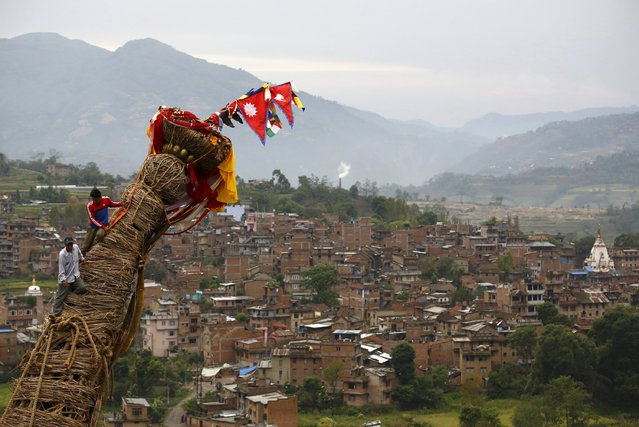 Bungamati village is pictured in the background as devotees sit on top of the chariot of Rato Machhindranath at Bungamati in Lalitpur, Nepal April 24, 2015. Rato Machhindranath is known as the god of rain and both Hindus and Buddhists worship Machhindranath for good rain to prevent drought during the rice harvest season. (Photo by Navesh Chitrakar/Reuters)