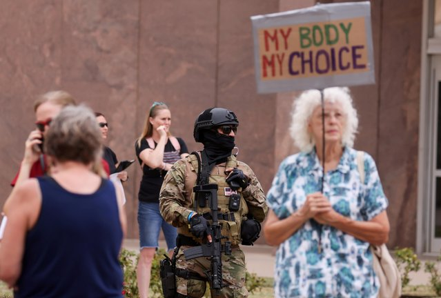 An armed civilian stands as people wait to get to the Senate chambers for the announcement of interim findings from a widely criticized audit of the 2020 election in Phoenix, Arizona, September 24, 2021. (Photo by Mike Blake/Reuters)