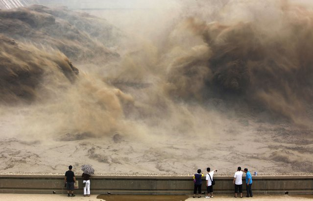 This picture taken on July 6, 2012 shows visitors gathering to giant gushes of water released from the Xiaolangdi dam to clear up the sediment-laden Yellow river and to prevent localized flooding, in Jiyuan, central China's Henan province. (Photo by AFP Photo)
