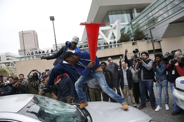 Protesters jump on a car at a rally to protest the death of Freddie Gray who died following an arrest in Baltimore, Maryland April 25, 2015. (Photo by Shannon Stapleton/Reuters)