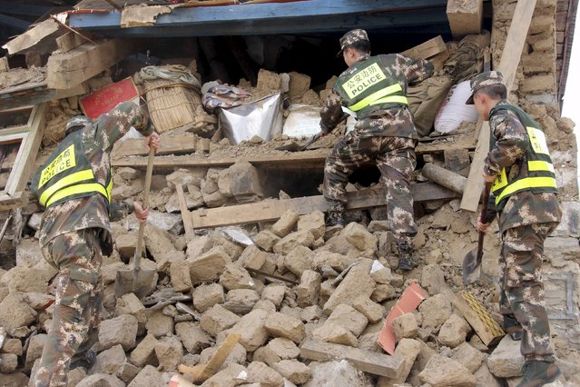 Police search ruins after a 7.9-magnitude earthquake hit Nepal on Saturday, in Gyirong county, Tibet Autonomous Region, China, April 26, 2015. (Photo by Reuters/Stringer)