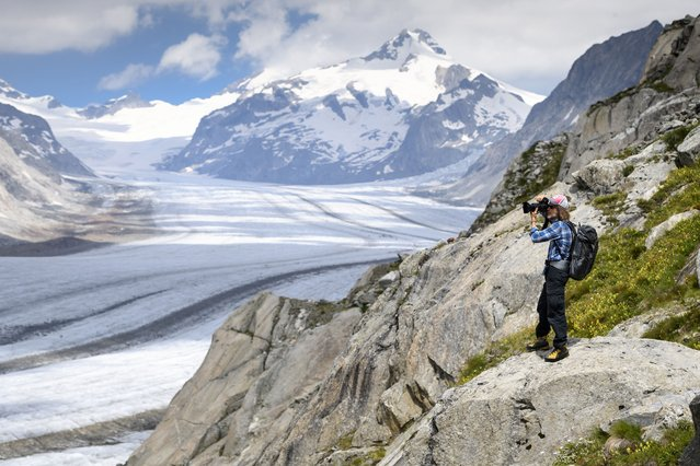 """In this July 21, 2020 file photo, Swiss photographer David Carlier takes photographs of the Swiss Aletsch glacier, the longest glacier in Europe, in Fieschertal, Switzerland. Swiss voters are casting ballots Sunday June 13, 2021, in a referendum on a proposed """"carbon dioxide law"""" that would hike fees and taxes on fuels that produce greenhouse gases, as their Alpine country experiences an outsized impact from the fallout of climate change. (Photo by Laurent Gillieron/Keystone via AP Photo/File)"""
