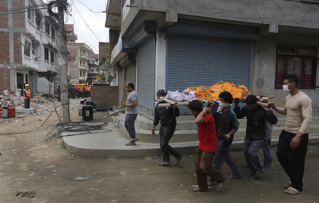 Nepalese relatives carry the body of an earthquake victim for cremation as Indian rescue workers, left in background, carry on their work in Kathmandu, Nepal, Tuesday, April 28, 2015. (Photo by Manish Swarup/AP Photo)