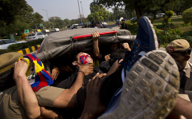 Tibetan exiles shouting anti China slogans outside the Chinese embassy are put in a police car as they protest to mark the 57th anniversary of the March 10, 1959, Tibetan Uprising Day, in New Delhi, India, Thursday, March 10, 2016. (Photo by Saurabh Das/AP Photo)