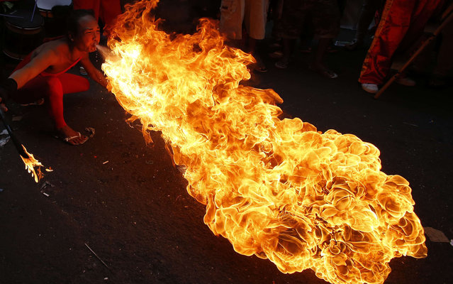 A performer blows fire during the Chinese New Year celebration in Manila's Chinatown January 31, 2014. According to the Chinese lunar calendar, the Chinese New Year, which welcomes the year of the horse, falls on January 31 this year. (Photo by Erik De Castro/Reuters)