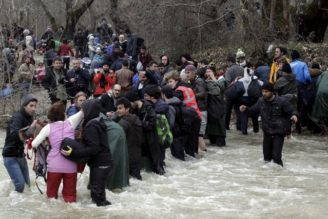Migrants wade across a river near the Greek-Macedonian border, west of the the village of Idomeni, Greece, March 14, 2016. (Photo by Alexandros Avramidis/Reuters)